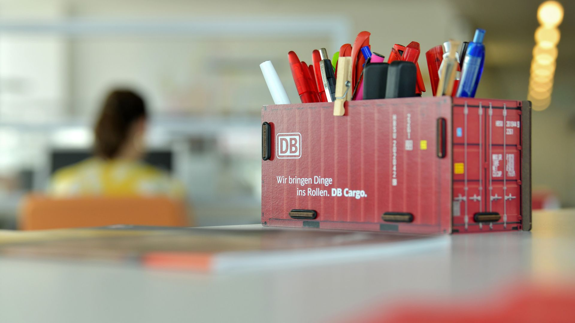 Callcenter-Agent, in front is a DB Cargo rail freight waggon as pen box