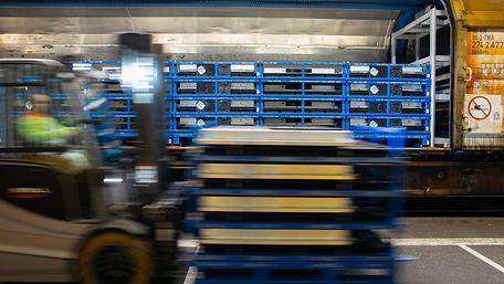 Güterwagen zum Transport von Batterien wird mit einem Gabelstapler beladen